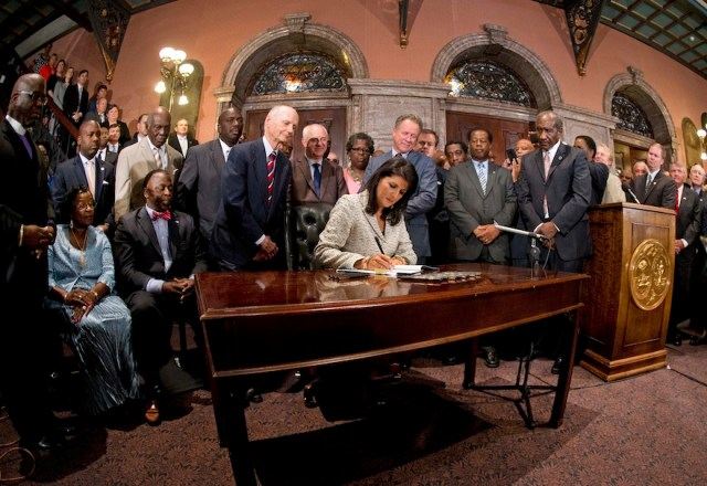 South Carolina Gov. Nikki Haley signs Senate Bill 897 into law, Thursday, July 9, 2015, at the Statehouse in Columbia, S.C. The law enables the removal of the Confederate flag from the Statehouse grounds more than 50 years after the rebel banner was raised to protest the civil rights movement. (AP Photo/John Bazemore)