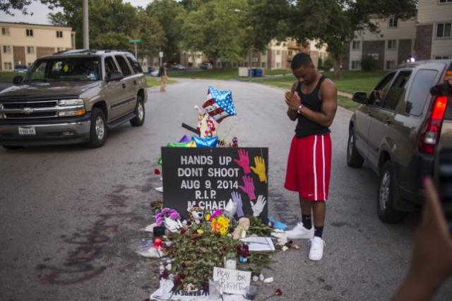 Local resident Ken Kendricks Jr. puts his hands together in prayer at a makeshift memorial at the site along Canfield Road where unarmed teen Michael Brown was shot dead in Ferguson, Missouri, August 22, 2014.   REUTERS/Adrees Latif/Files