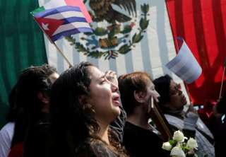 A supporter of Fidel Castro reacts as she attends a tribute ceremony, following the announcement of the death of Cuban revolutionary leader Castro outside the Cuban Embassy, in Mexico City