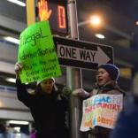 What's the real danger here? One woman indicates it's the current administration during a huge protest outside Kennedy Airport in Queens Saturday night following President Trump's ban on travel from various mostly-Muslim countries.