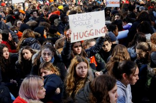 Students from Fiorello H. Laguardia High School sit down on West 62nd street in support of the National School Walkout in the Manhattan borough of New York City, New York, U.S., March 14, 2018. REUTERS/Mike Segar - RC1DA90879E0