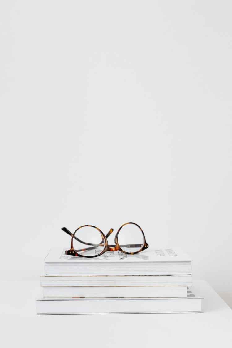brown framed eyeglasses on books