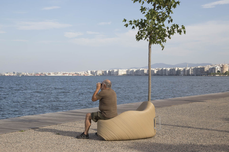 A man watching the water in Thessaloniki, sitting on a 3D printed street chair with integrated bike rack.  Photo via The New Raw.