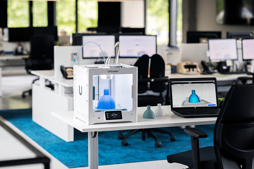 An Ultimaker S3 3D printer on a desk with a project being printed out