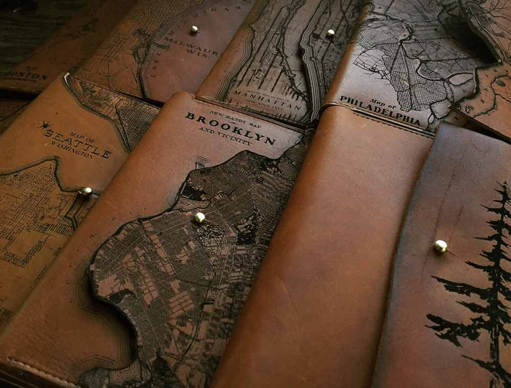 An image of laser etched leather journals from Tactile Craftworks