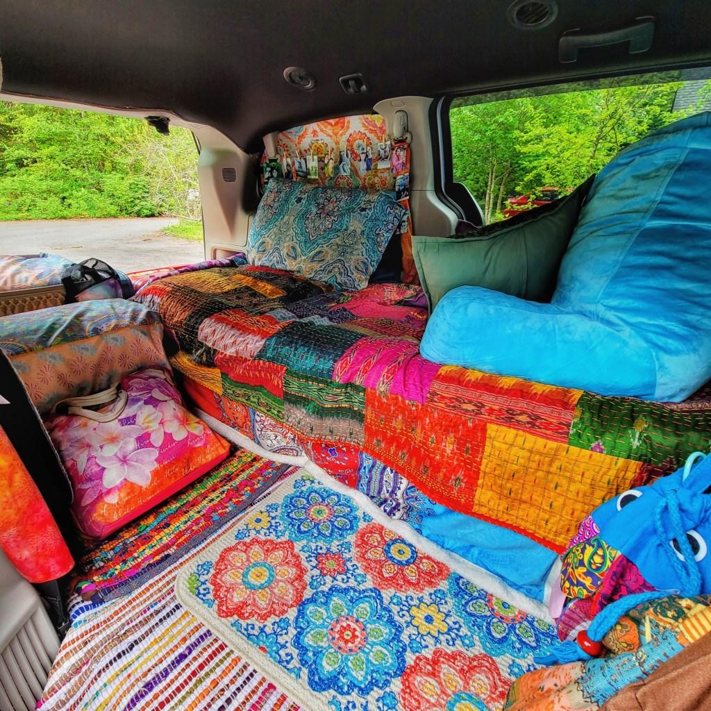 The inside of a converted Dodge Grand Caravan camper van in Boho style