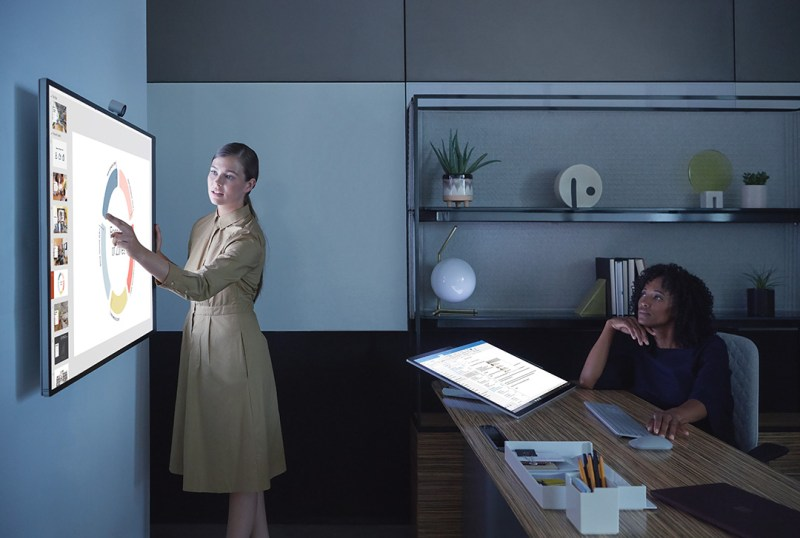 A woman uses a Surface Hub 2S that is mounted to a wall in an office