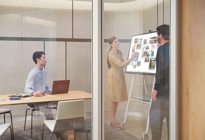 A woman uses Surface Hub 2S in an office as two men look on