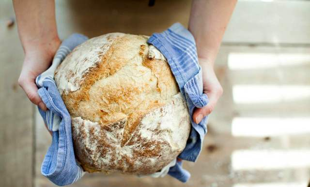Person holding baked bread covered with towel | Your Road Map To Self Sufficiency