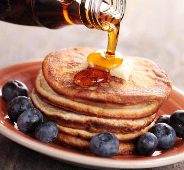 Close-up of pouring maple syrup on stack of pancakes   Survival Food Items That Will Outlast The Apocalypse