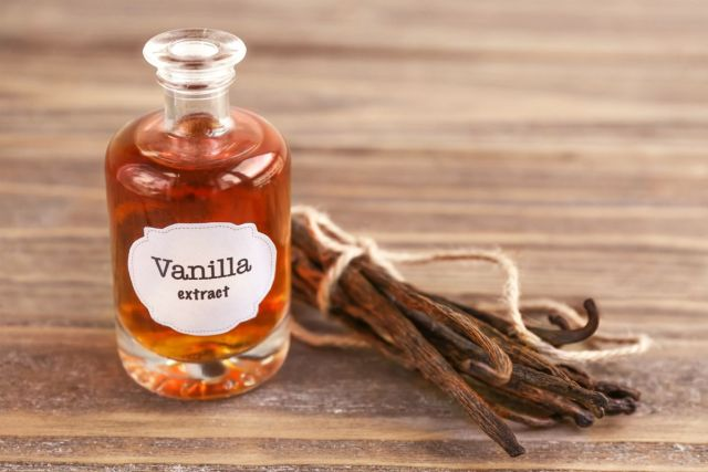 Bottle with aromatic extract and dry vanilla beans on table | Survival Food Items That Will Outlast The Apocalypse