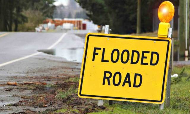 Yellow sign that the road is flooded   Flood Survival Tips   How To Survive Before, During, And After A Flood