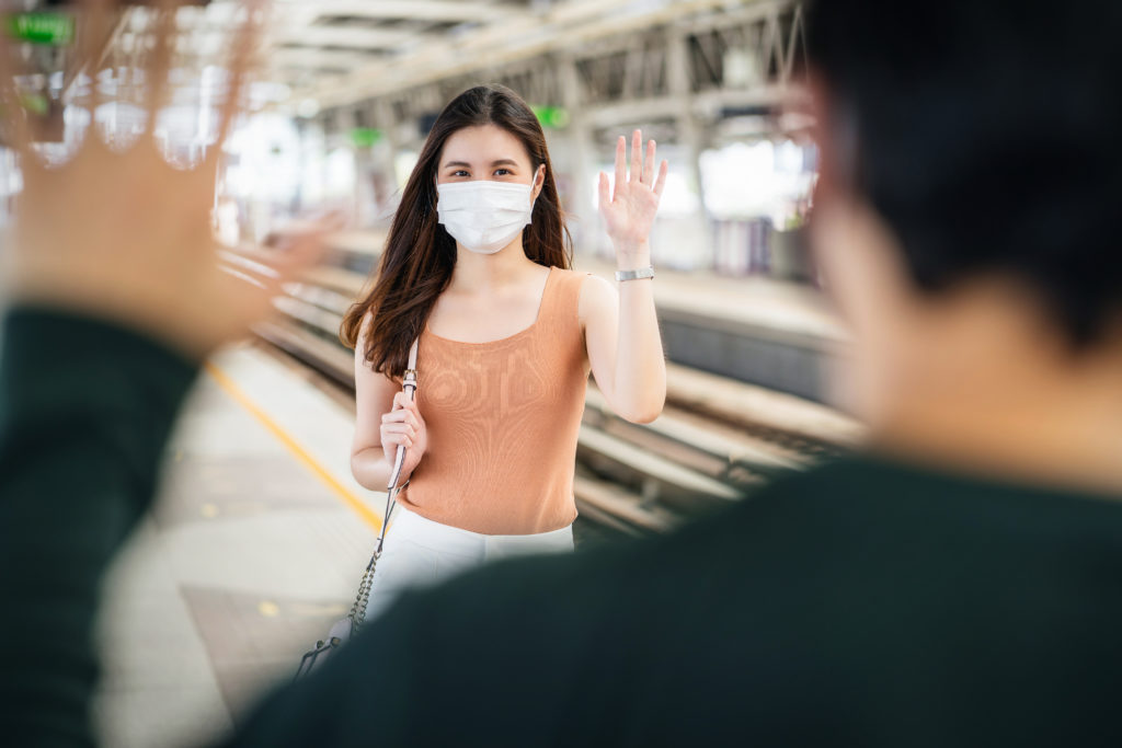 Young woman waring a mask smiling and waving to create connection with another person.