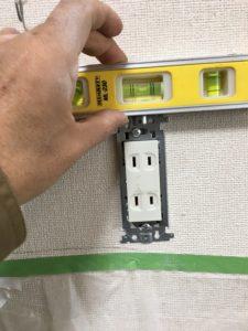 取り付けたコンセントが斜めにならないようにレベルで水平を測ります。