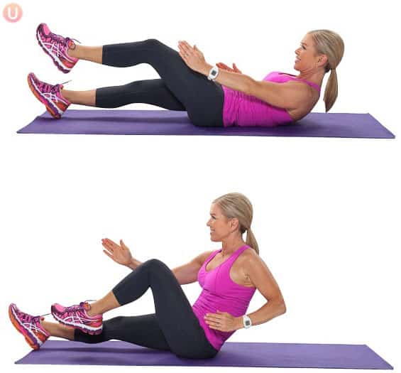 Chris Freytag demonstrating a sprinter sit-up exercise in pink tank top and black yoga pants.
