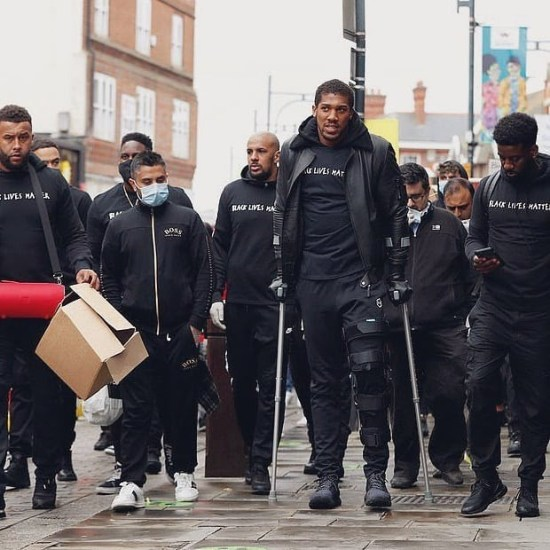 Anthony Joshua walks on crutches with Black Lives Matter protesters