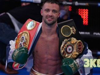Josh Taylor flaunts the WBA and IBF belts after victory