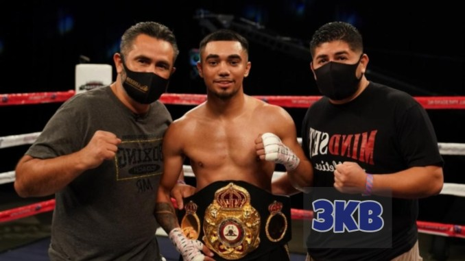 Saul Sanchez takes a picture with his trainer and second assistant.