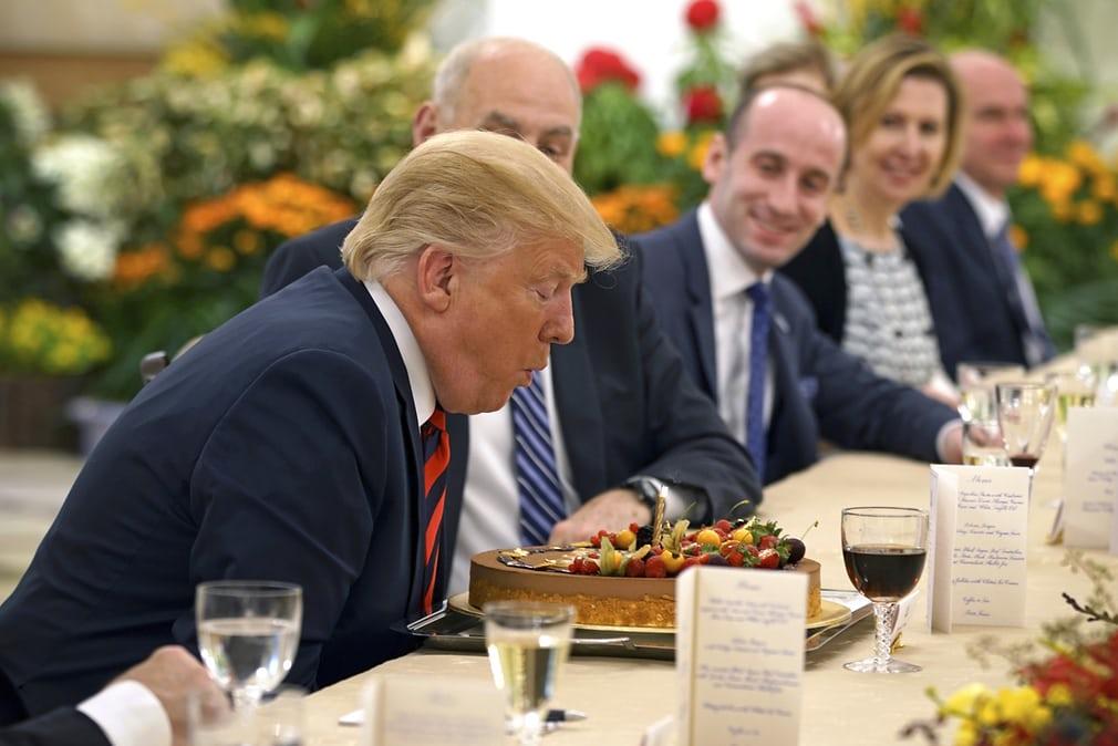 Президент США Дональд Трамп задмухує свічки на торті з нагоди дня народження
