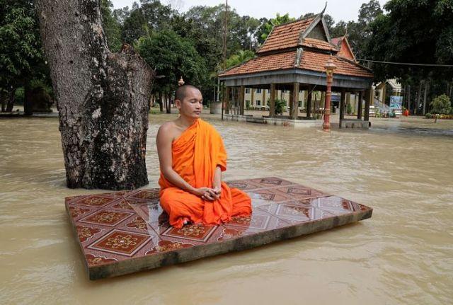 Буддійський монах медитує на подвір'ї затопленої повінню пагоди