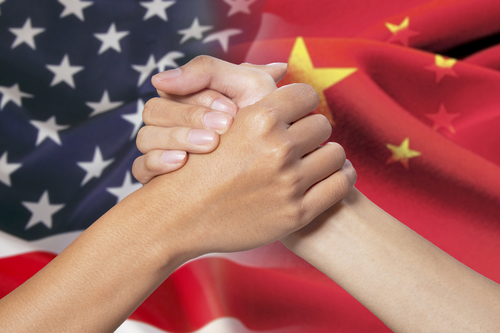 Two hands with partnership poses in front of the russian and american flags