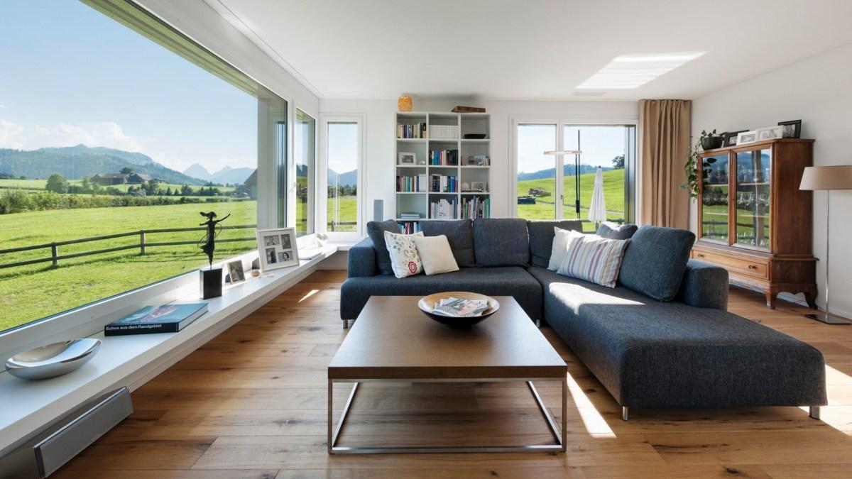 Wohnzimmer mit dunkelgrauem Sofa, braunem Tisch und grossem Sitzfenster