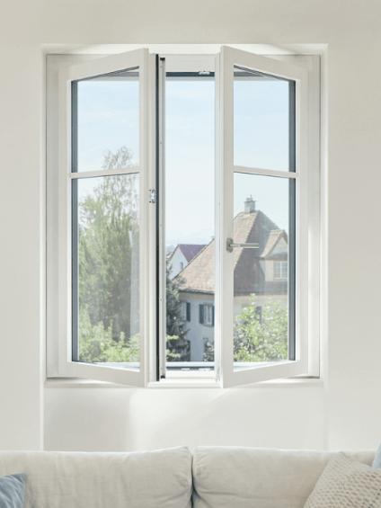 Weisses Renovationsfenster RF1 offene Flügel und weisses Sofa steht davor