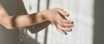 Hand mit Betonwand und Lichtspiel durchs Fenster