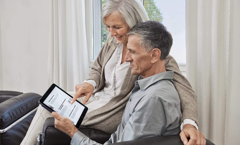 Älteres Ehepaar sitzt zusammen und schaut gemeinsam auf ein Tablet