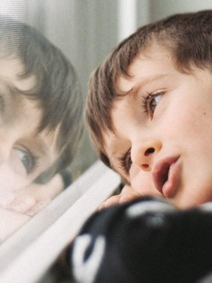 Kleiner Junge blickt verträumt aus Fenster