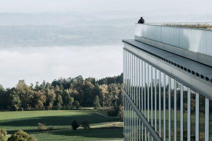 Homme debout sur la terrasse de la clinique de rééducation de Bellikon, regardant le paysage.