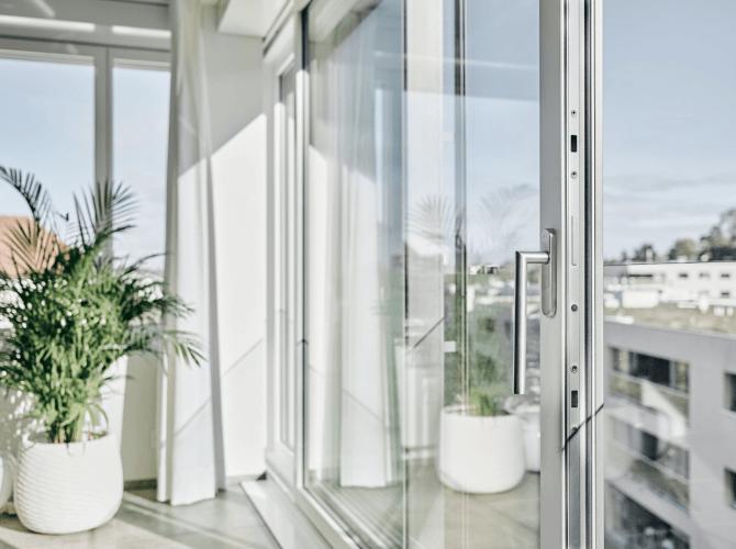Grosse Fenster mit Aussicht und grüner Pflanze und weissen Vorhänge