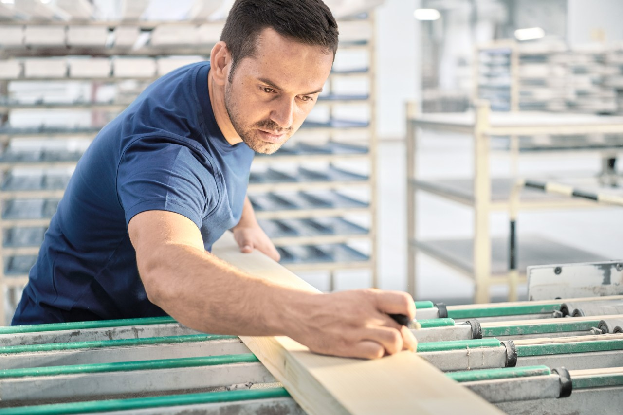 Un employé de 4B chargé de la production des fenêtres vérifie la qualité du bois.