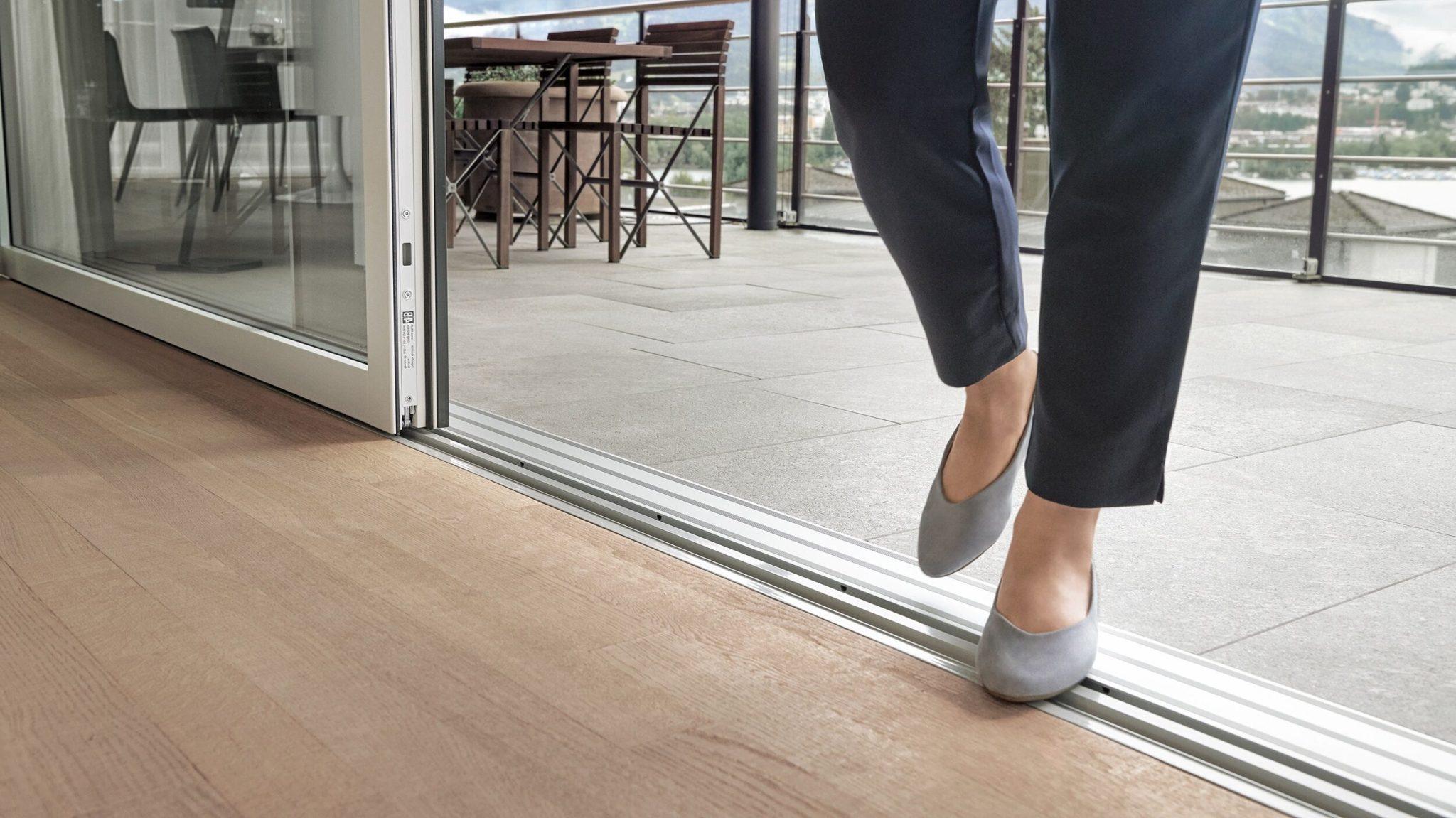 Une femme court au-dessus du seuil zéro de la porte coulissante ST1