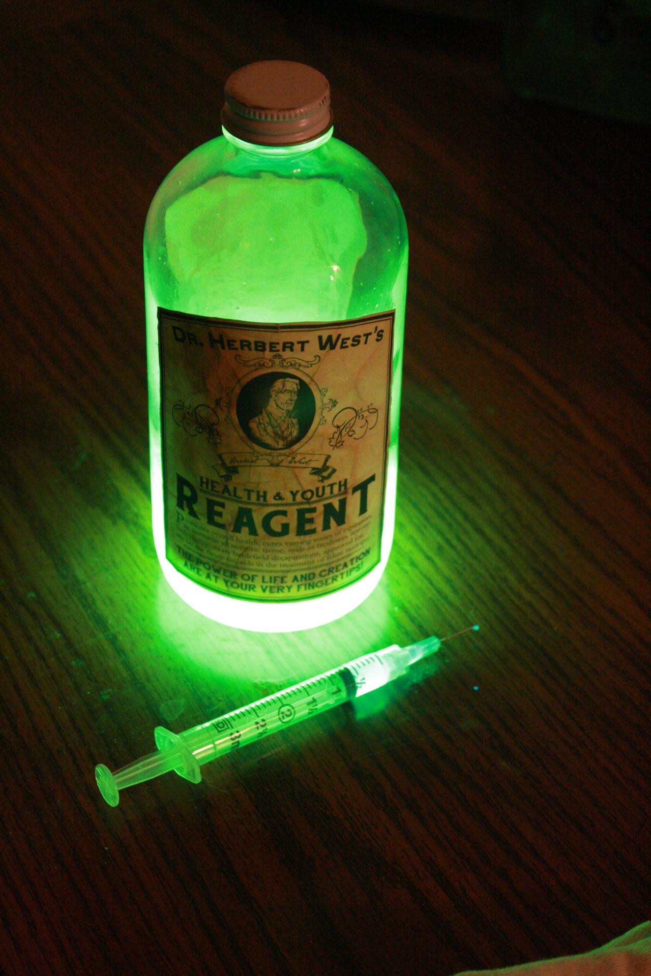 "The Innsmouth Trading Company is very excited to reveal out latest acquisition! From the estate of the late Dr. Herbert West we have acquired several cases of his patented ""Health and Youth Reagent"". This fluorescent yellow-green liquid is extremely reactive to ultraviolet light, and is said to contain the secrets to life itself. The reagent comes packaged in clear, 16 oz. glass bottles; the labels -containing instructions for use and a list of potential side-effects- have naturally browned with age. We will be offering bottles of this potent elixir for sale at several up-coming events and on our online storefront. Check back often for more information! NOTE: Reagent is not suitable for consumption by the living."
