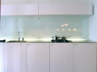 A clear glass backsplash is often seen in modern ...