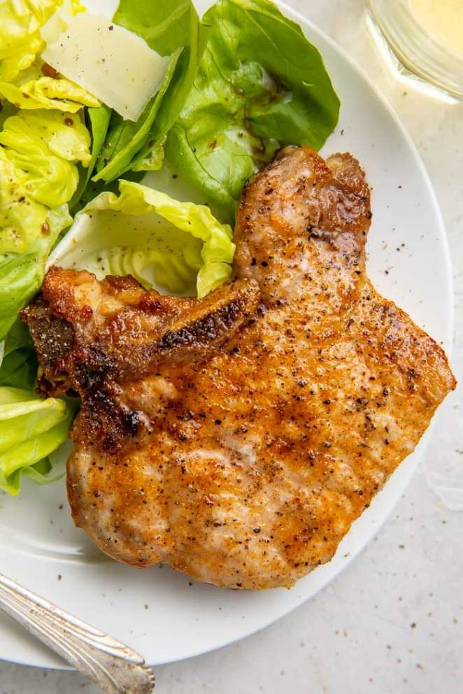 A pork chop on a plate next to some lettuce