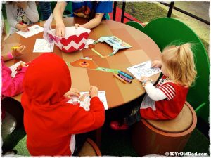 Kids colouring pictures at the Hey Duggee Drawing Badge table