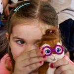 Girl hides behind her Jeanette Chipmunk plush-toy