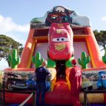 Daddy waits for his kids to come down the Lightning McQueen slide.
