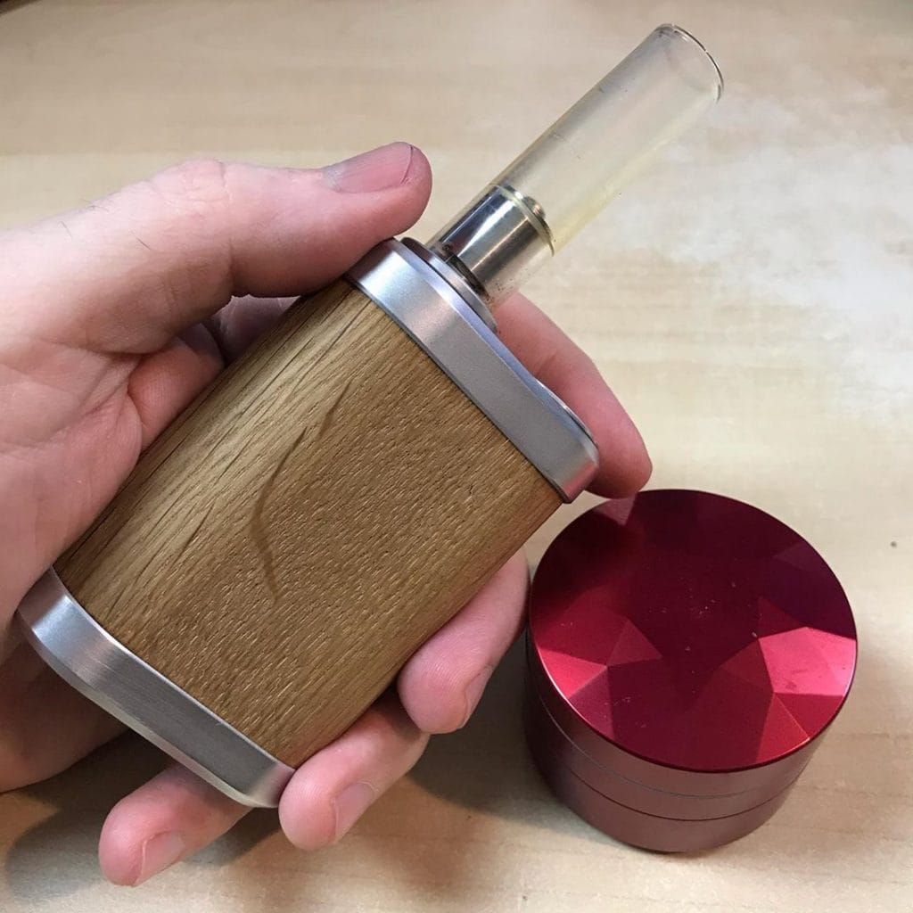 Tinymight vape in hand, next to Brilliant Cut grinder