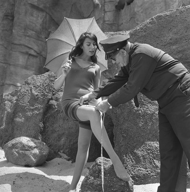 PRECAUTIONARY MEASURE-Policeman Chuck Peyton checks to see if the old-fashioned bathing suit worn by actress Myrna Ross complies with 1933 Redondo Beach ordinance banning women's suits that are more than 3 in. above knee. The city attorney warned enforcement may be necessary if topless suits appear on beaches. Male swimmers would also be required to wear more discreet attire.
