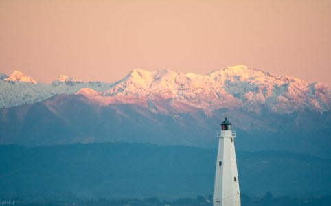 snowy peaks behind lighthouse nelson new zealand, sv cavalo