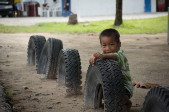 marshallese boy playing behind tire, sv cavalo