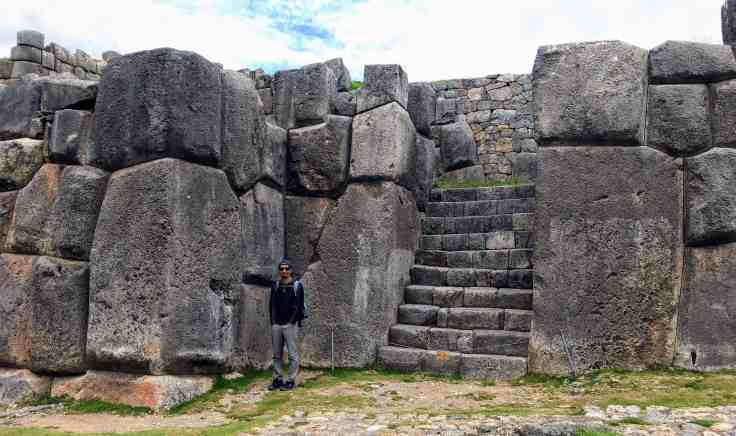 Trin next to massive stones of Sacsayhuaman ancient Inca ruins