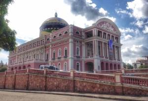 Manaus Theater located in the heart of the Amazon Jungle. It is a large pink building with a mosaic dome on top.