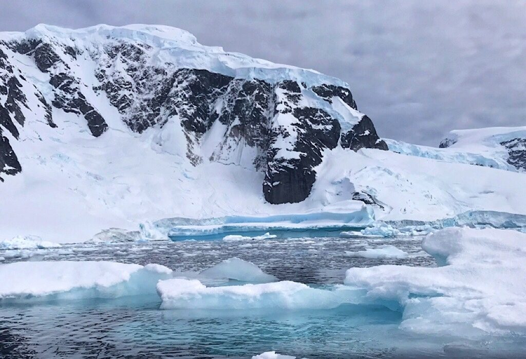 Icebergs and a snowy mountain in Antarctica