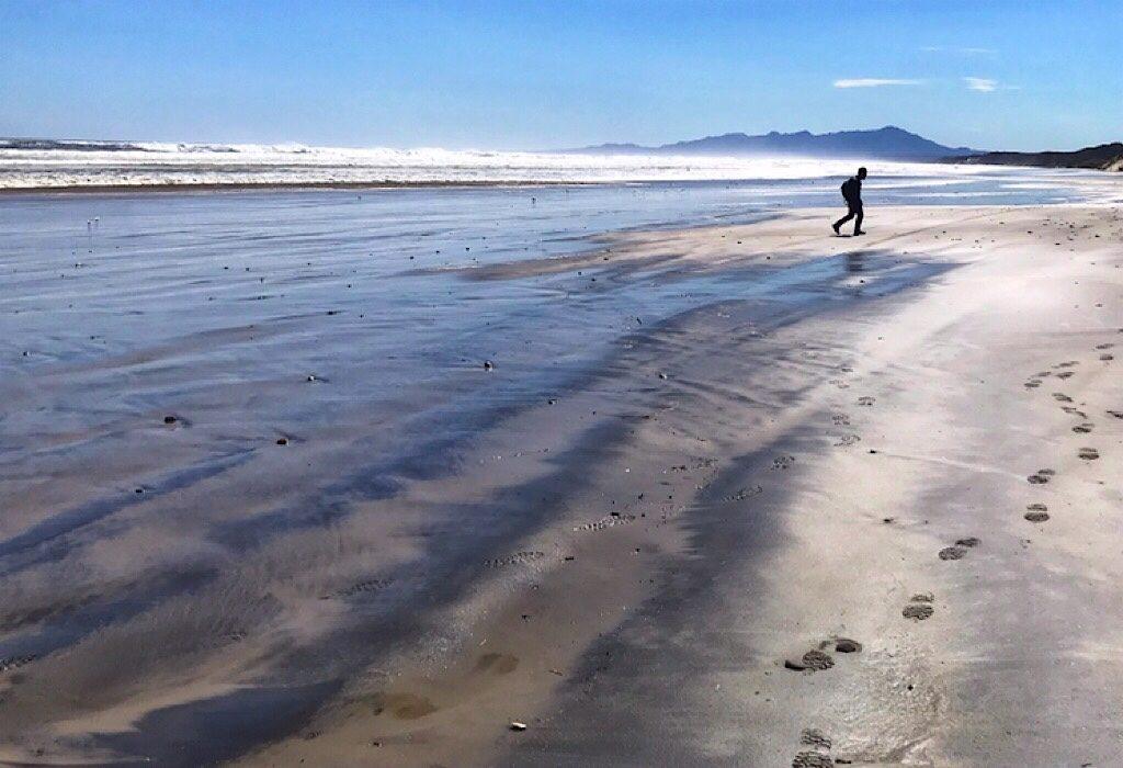 Trin walking on the beach at Hells Gates in Tasmania, Australia