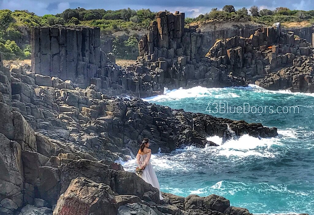 Bride standing among basalt lava by the Kiama coast line