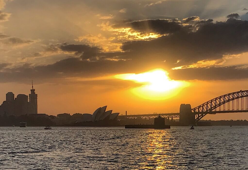Sydney at sunset with the Opera house in the distance